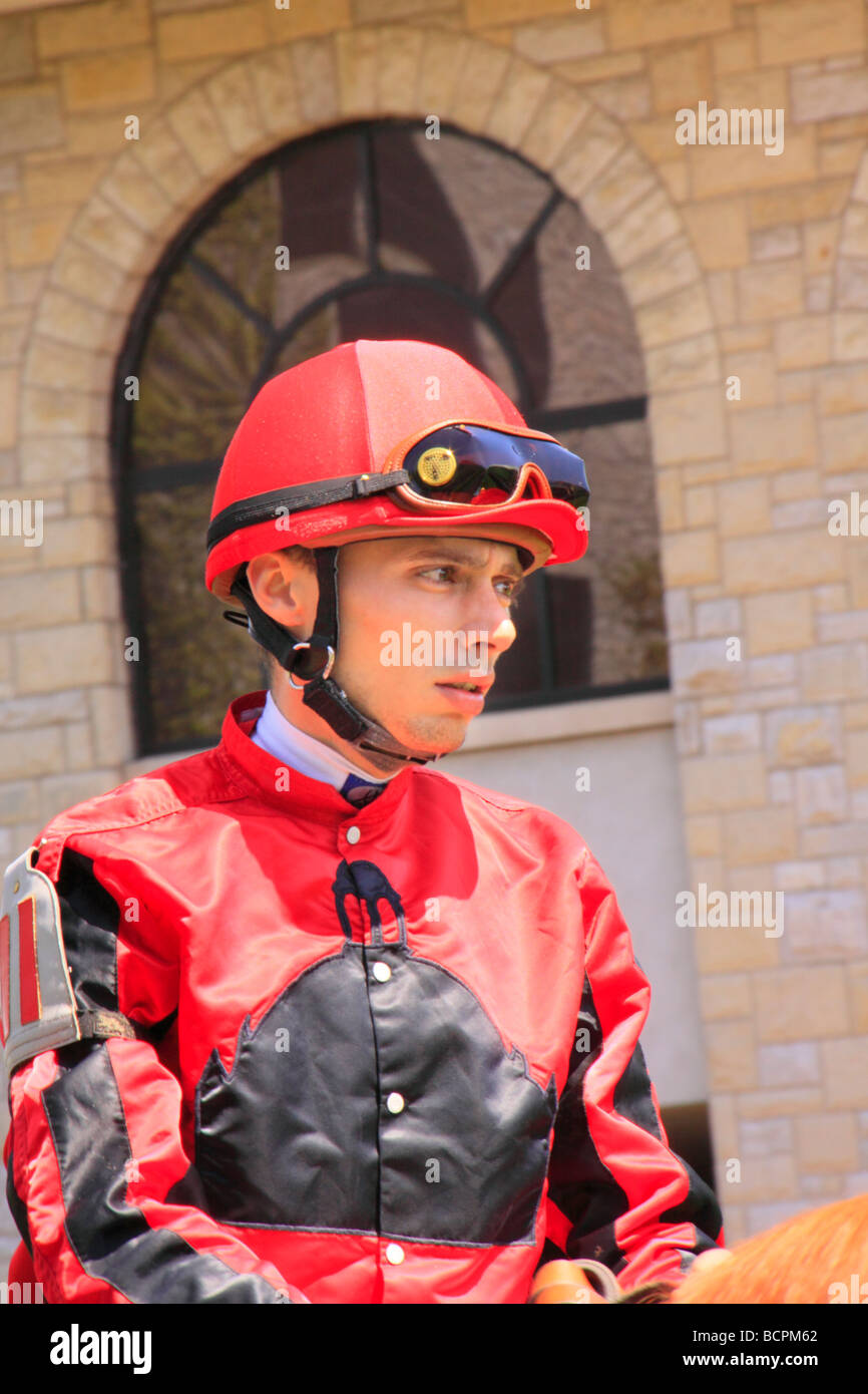A jockey rides his thoroughbred from the paddock onto the track at Keeneland Race Course Lexington Kentucky - Stock Image