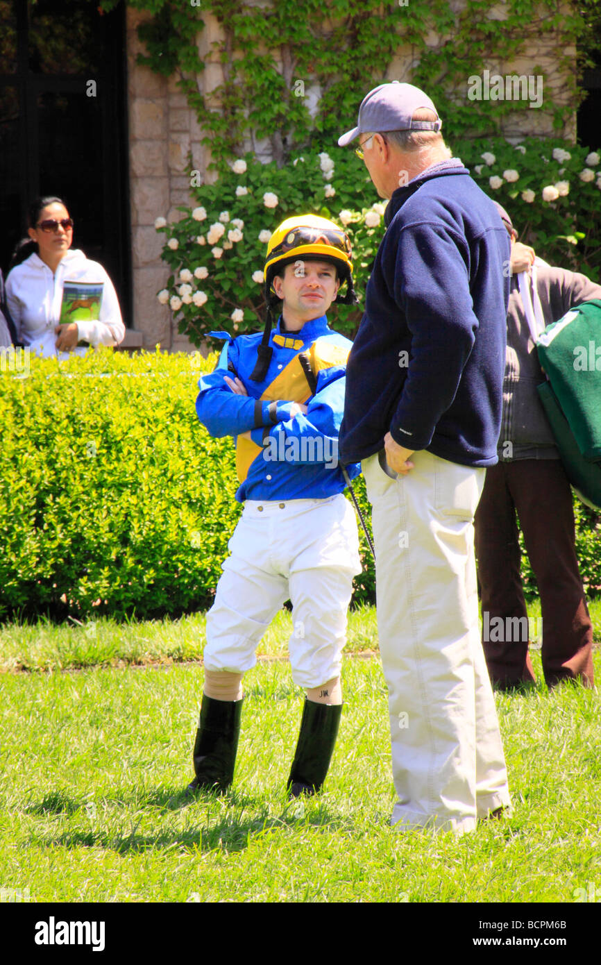 A thoroughbred trainer and jockey talk in the paddock before a race at Keeneland Race Course Lexington Kentucky - Stock Image
