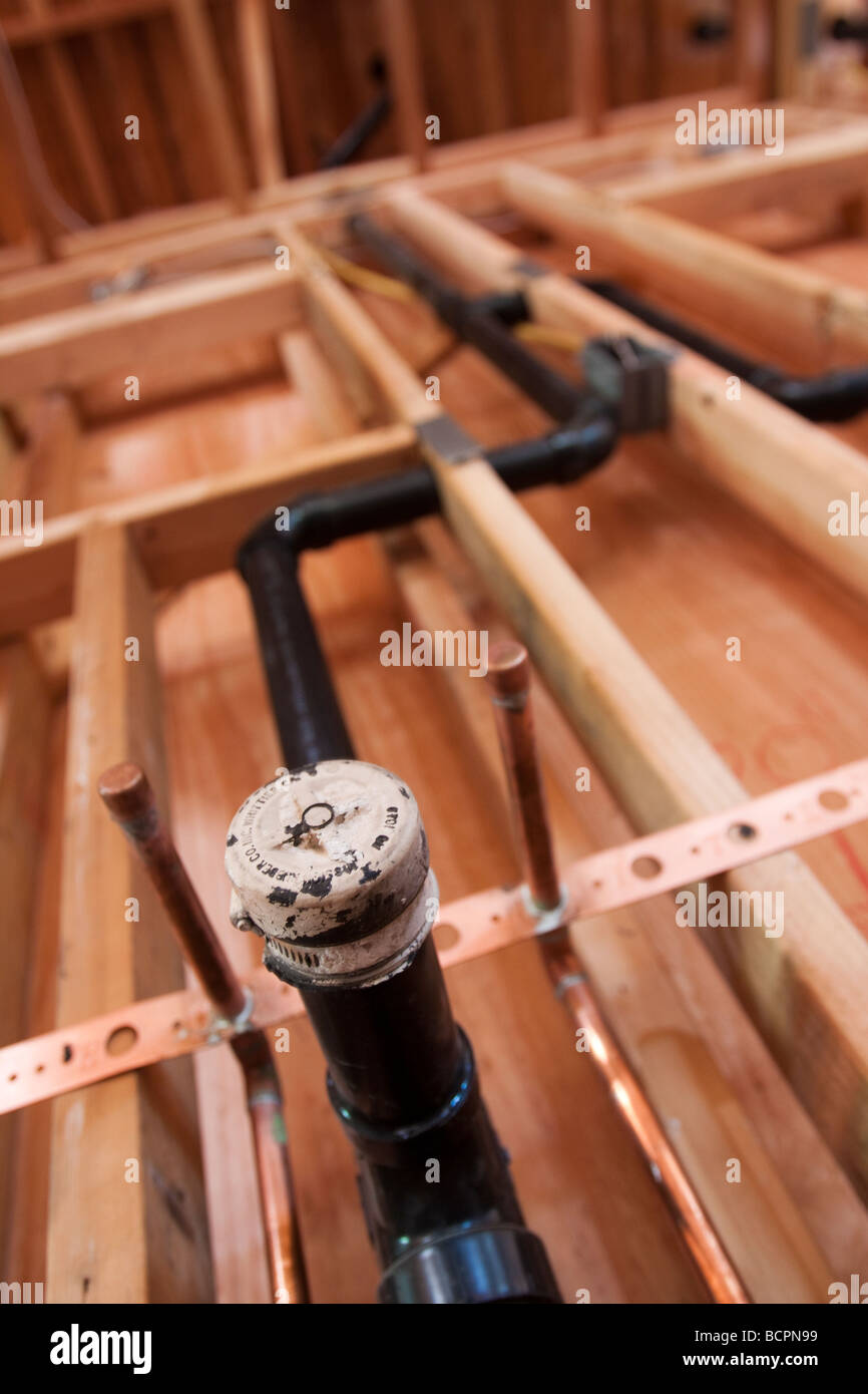 Rough plumbing pipes and drain installed in a wall at residential construction site - Stock Image