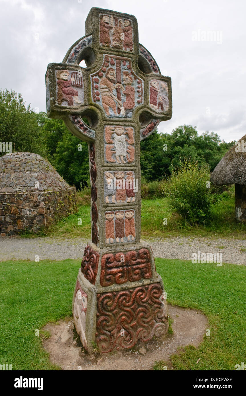 Ornate painted celtic cross with a depictino of Saint Patrick in the centre,at a monastic village in the Irish National - Stock Image