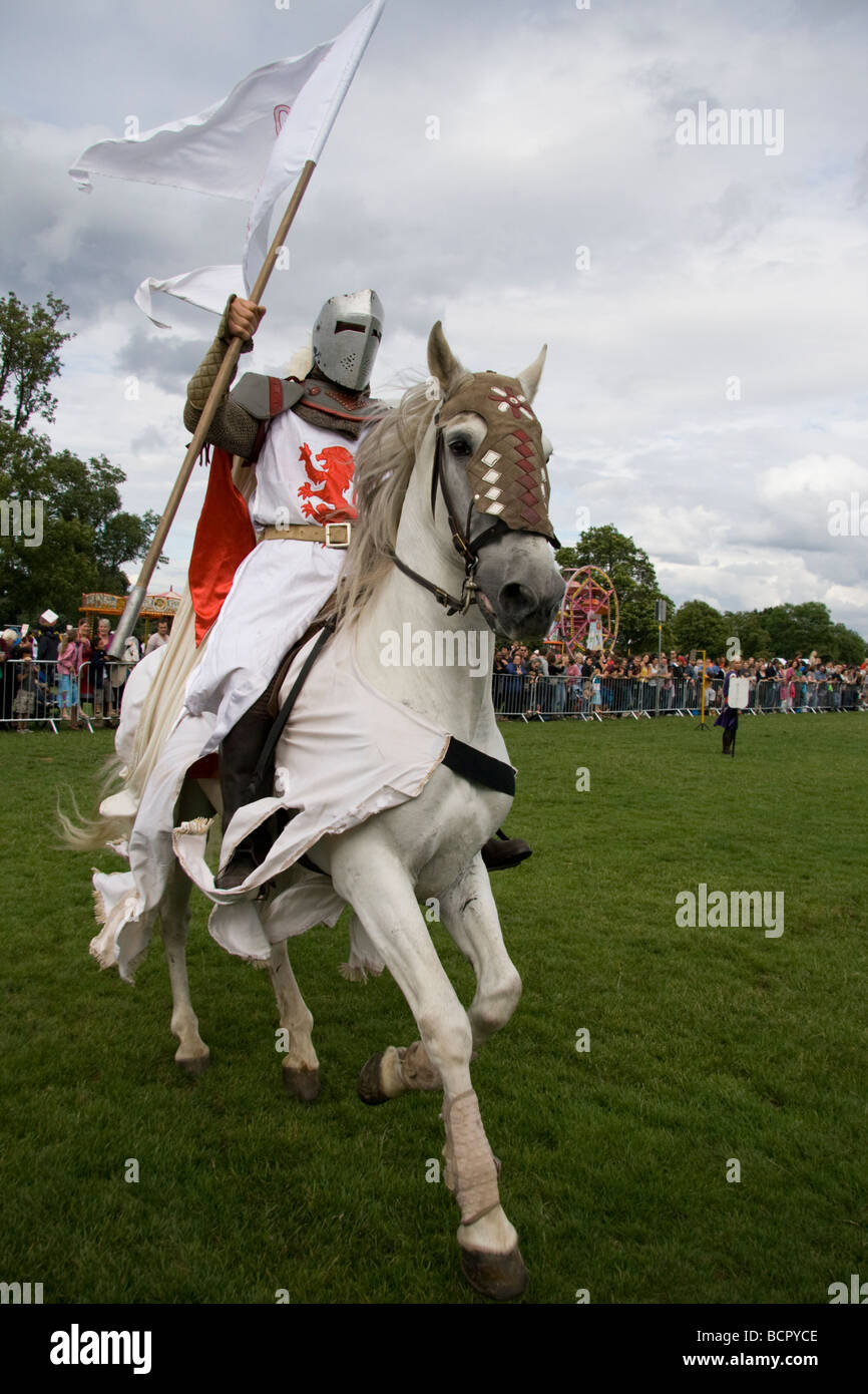 Medieval knight galloping on horseback holding the standard aloft in triumph.Lambeth Country Show, London, England,18th - Stock Image