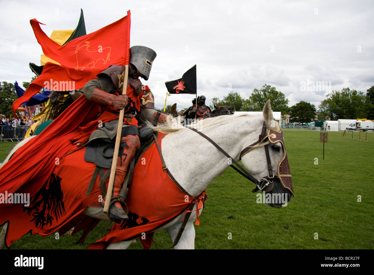 Medieval knights on galloping horses carrying standards or flags, Lambeth Country Show, London, England, UK.  18th - Stock Image