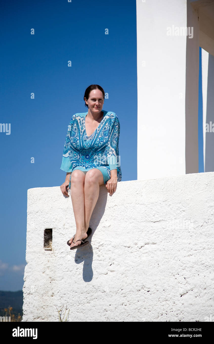 8eb8518536537 Woman in Blue kaftan sits on white wall in Greece - Stock Image