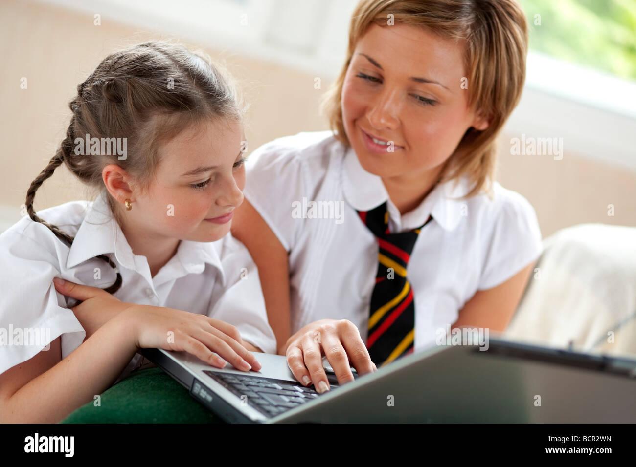 2 girls using on laptop - Stock Image