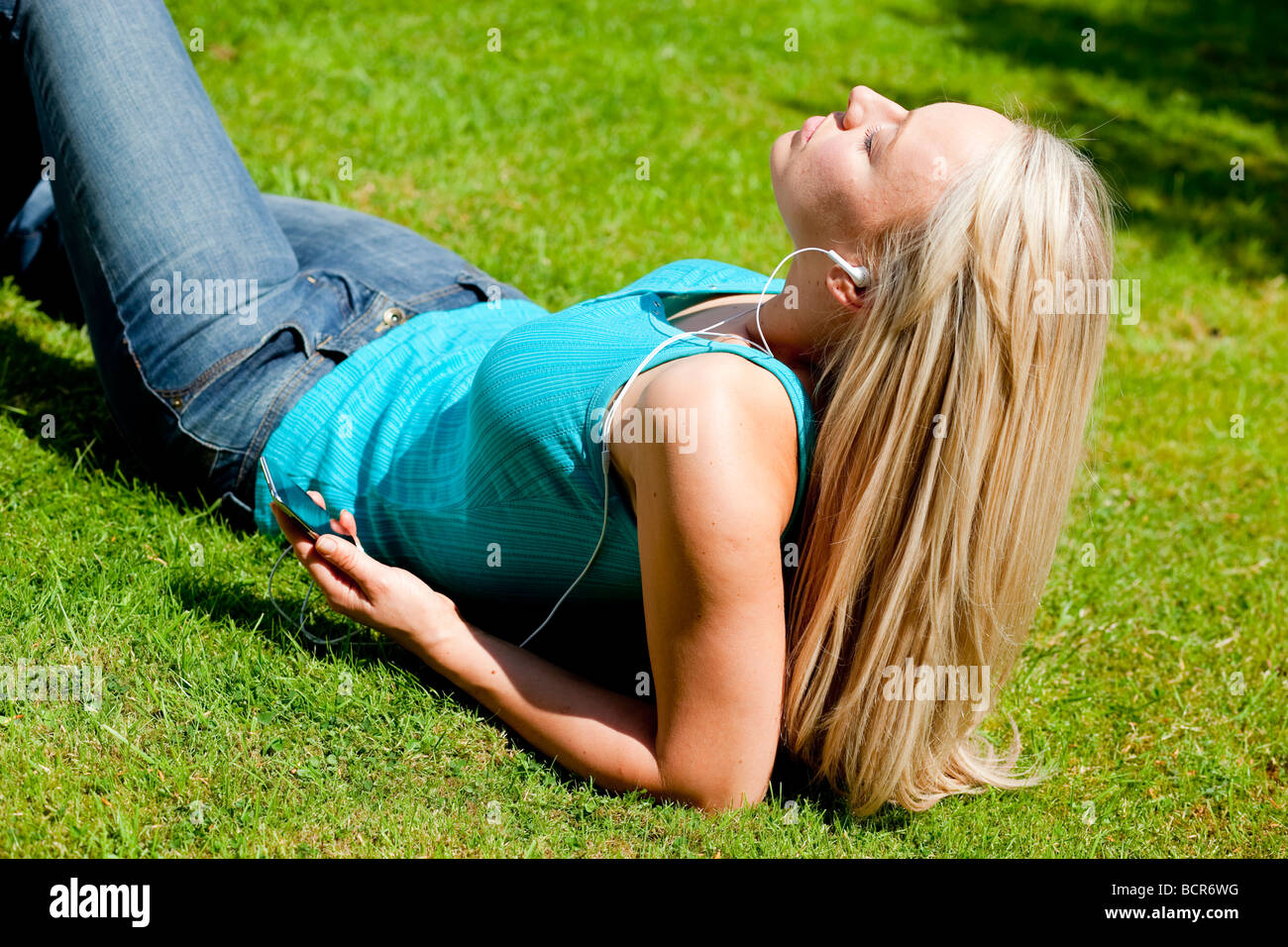 Girl lying on grass listening to mp3 player - Stock Image