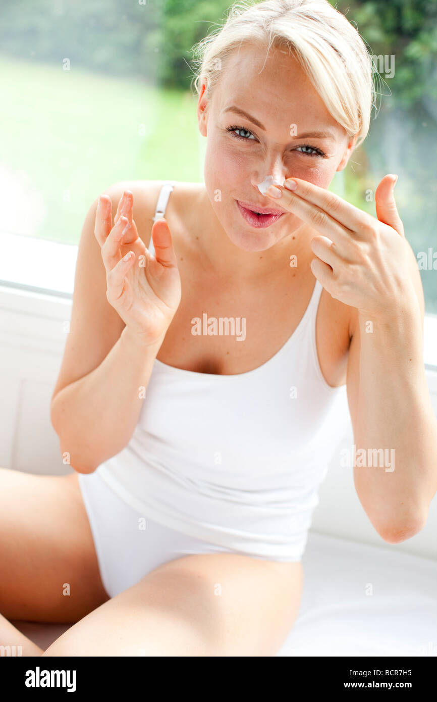 Girl applying moisturizer to face - Stock Image