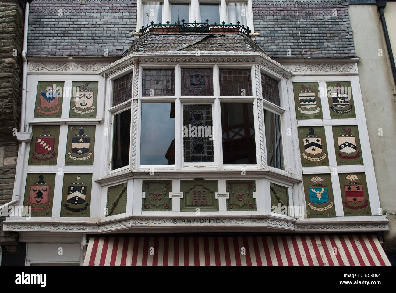 Family crests above a shop front, in Dartmouth, Devon - Stock Image