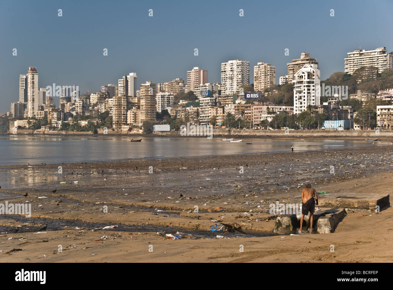 A homeless person washing on the Mumbai beach - Stock Image