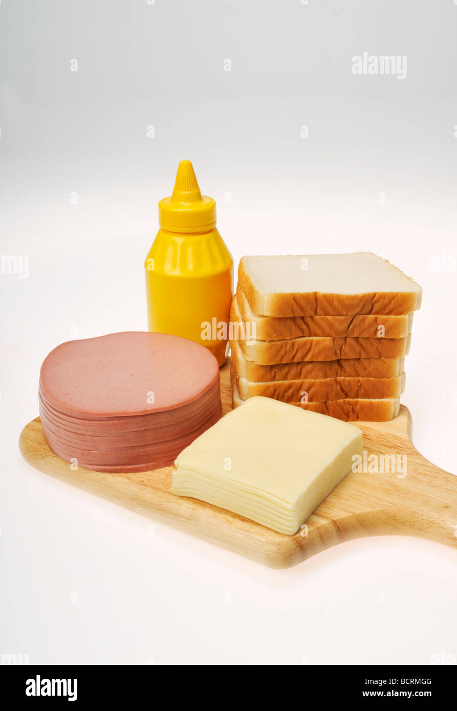 Ingredients for a bologna and cheese sandwich with stack of deli meat, cheese, bread and mustard on wood board - Stock Image