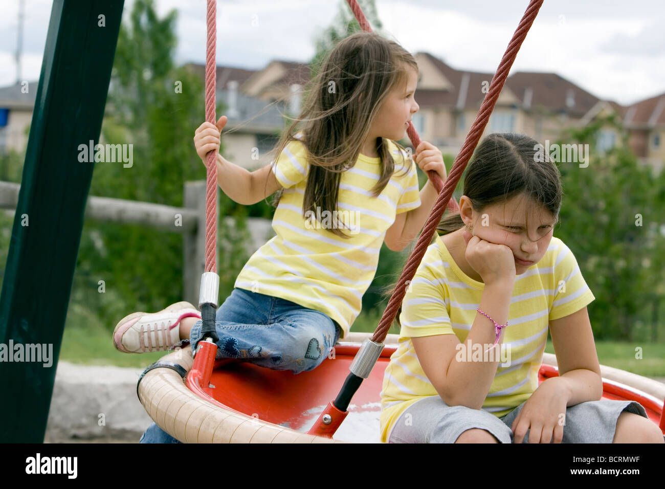 2 sisters on swing - Stock Image