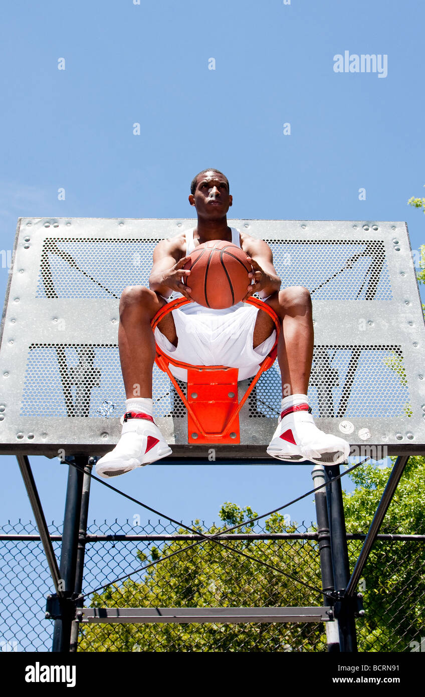 Handsome sporty African American male basketball player dressed in white and holding his ball outdoor on a summer day Stock Photo