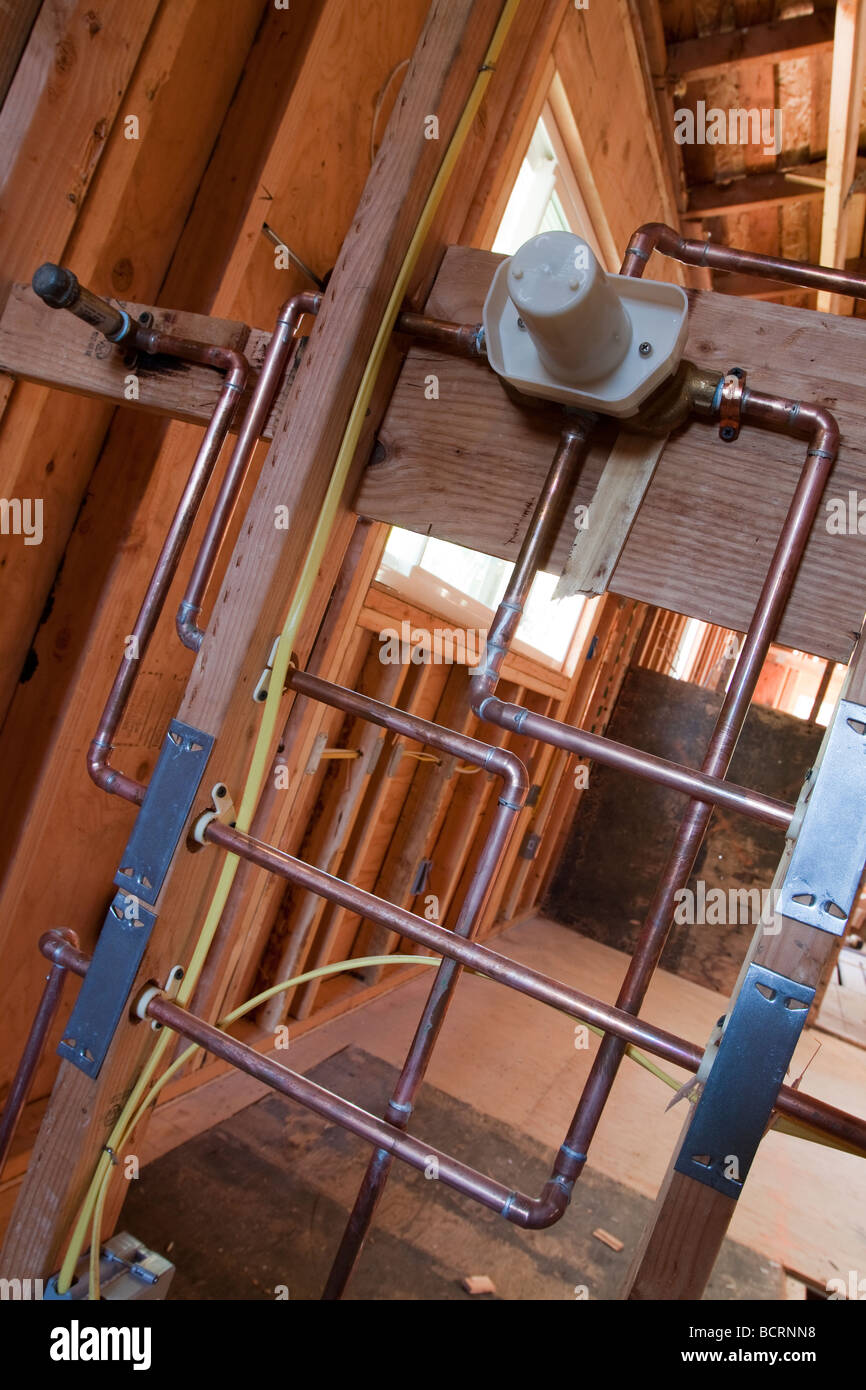 Copper plumbing for shower intalled in a wall at residential construction site - Stock Image