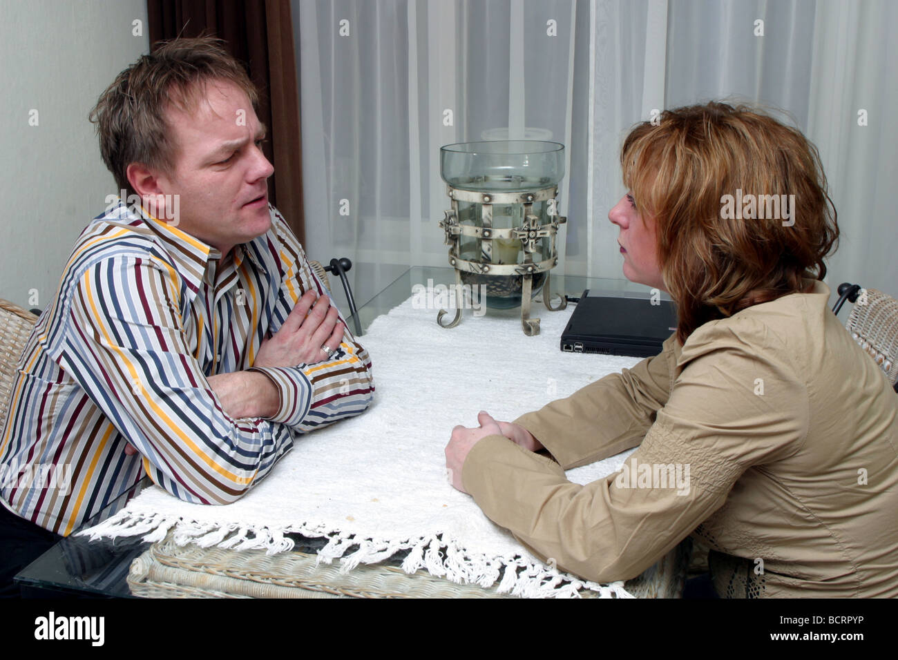 Husband and wife talking seriously, having an argument, coping difficulties, might be divorce. Stock Photo