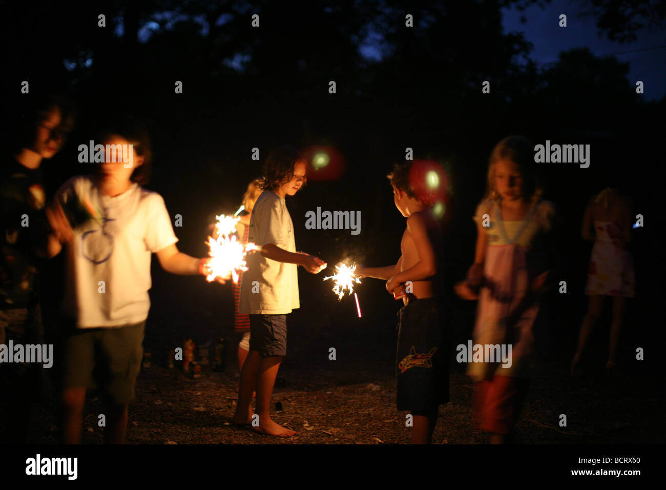 Children lightning sparklers at 4th of July party - Stock Image