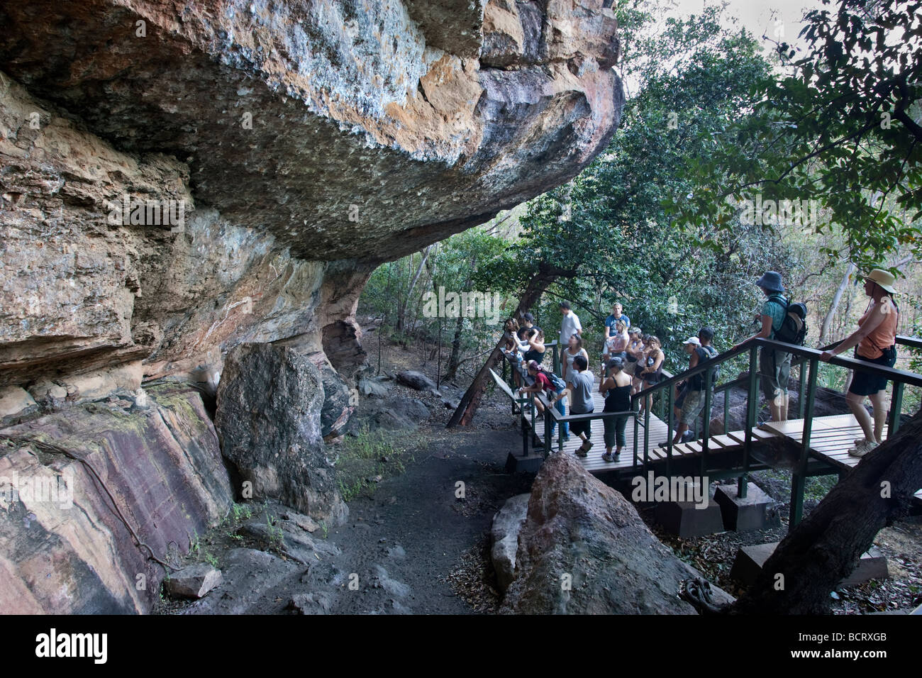 A group of tourists listening to a talk and looking at Aboriginal rock art at Anbangbang Gallery at Nourlangie Rock. - Stock Image