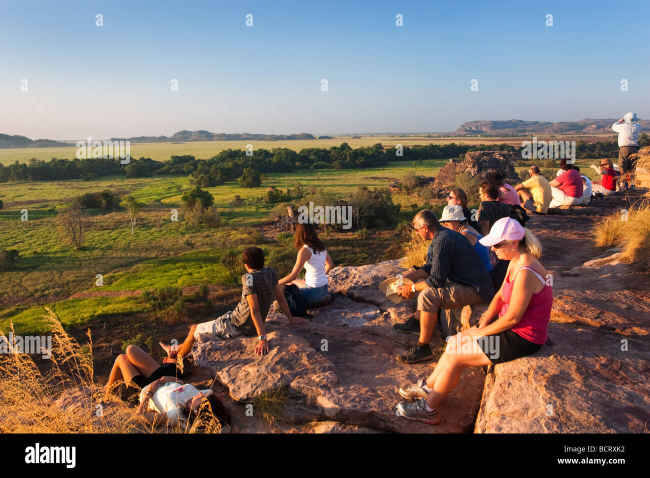 Tourists waiting for the sun to set from the top of Ubirr Rock in Kakadu National Park - Stock Image
