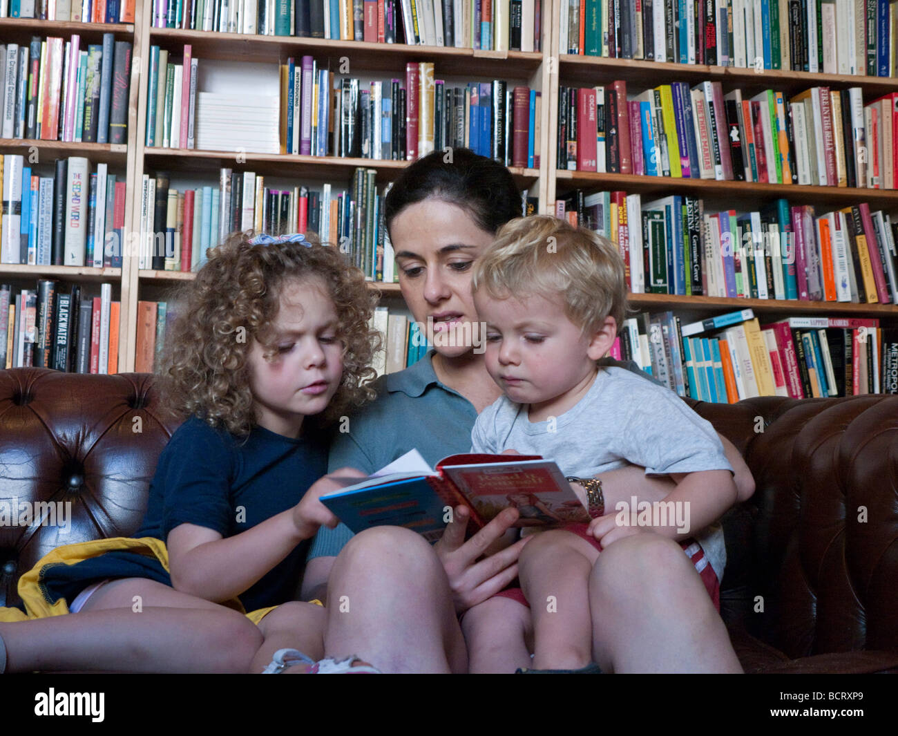 Mother reads to her two young children in secondhand bookshop in bohemian district of Prenzlauer Berg in Berlin - Stock Image