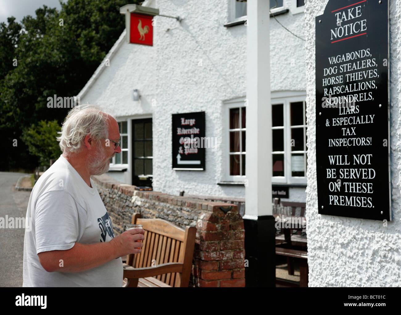 Man reading an amusing notice outside the Barley Mow public house, Tilford, Surrey, England, UK. - Stock Image