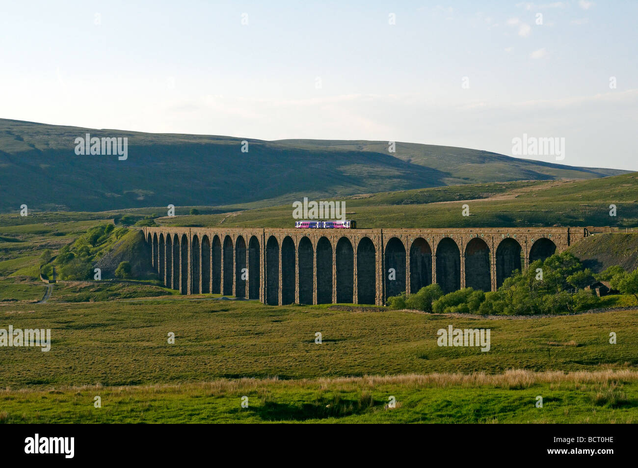 The Ribblehead Viaduct in the Yorkshire Dales with a small train crossing the viaduct - Stock Image