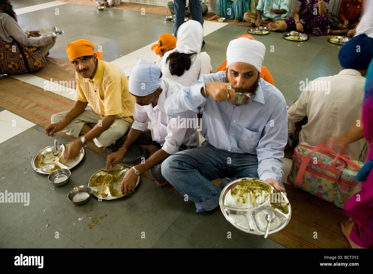 Sikh men eating a free meal served in the Community kitchen at the The Golden Temple (Sri Harmandir Sahib) Amritsar. Stock Photo