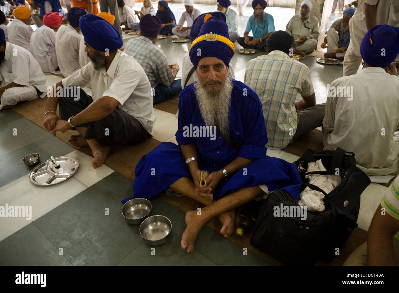 Sikh man waits to eat a free meal at the Community kitchen in the Golden Temple (Sri Harmandir Sahib) Amritsar. Stock Photo