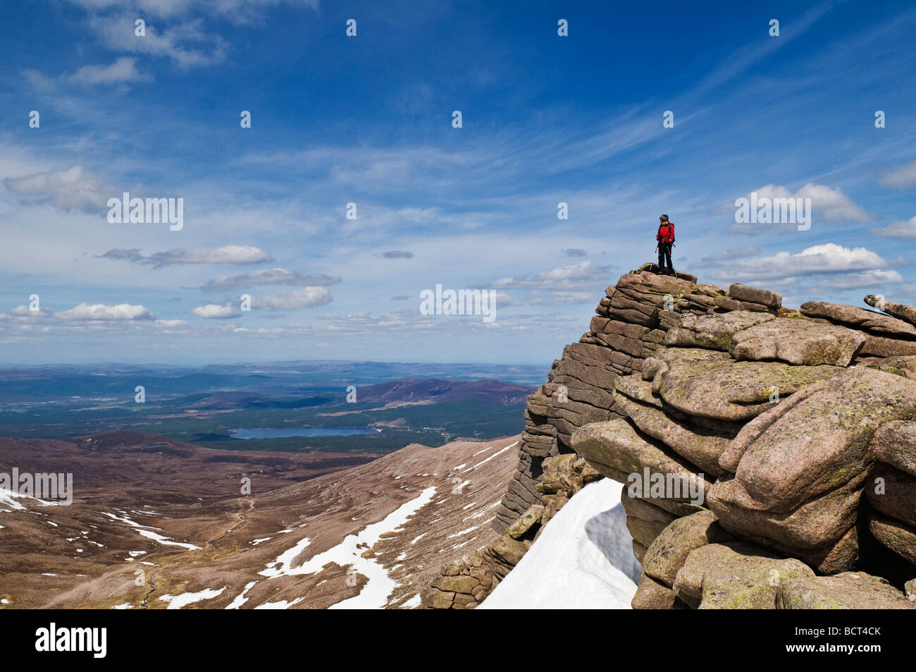 Female hiker stands on rocky outlook and enjoys view, Cairngorms national park, Scotland - Stock Image