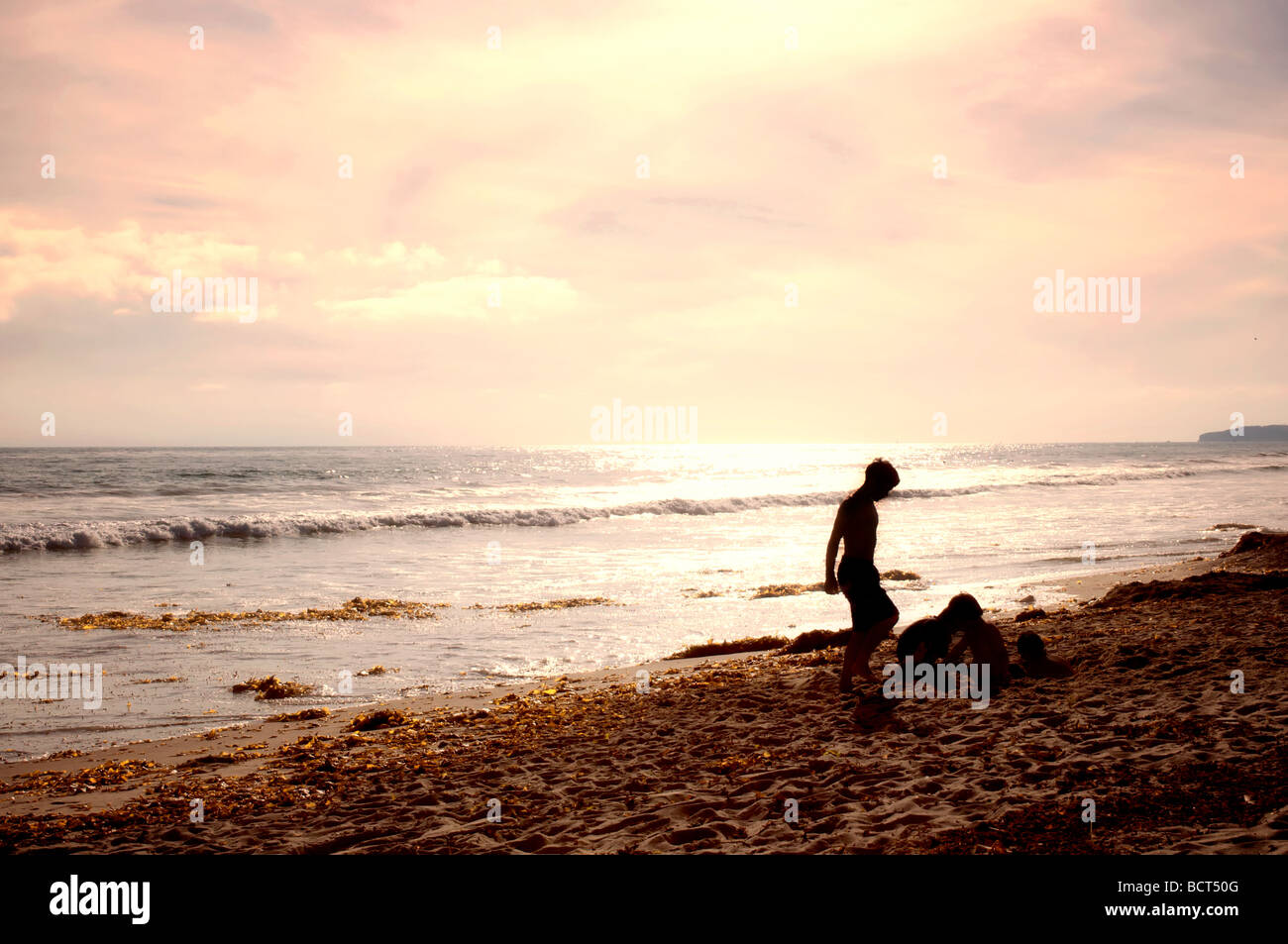 Warm Southern California summer afternoon, kids digging the sandy beach at San Clemente. Stock Photo