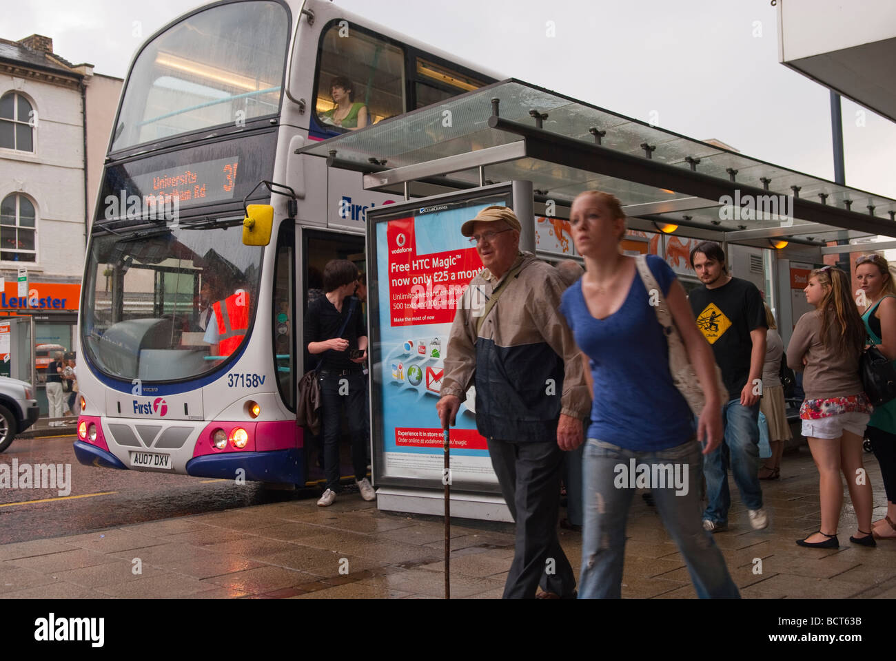 A bus stop in the city centre in Norwich Norfolk Uk with people getting wet in the pouring rain Stock Photo