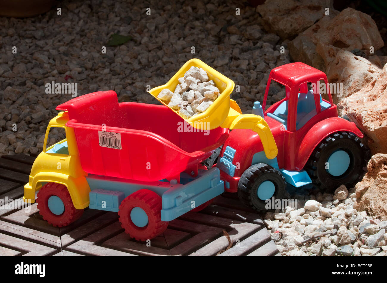 Toy digger and truck in pretend quarry. - Stock Image