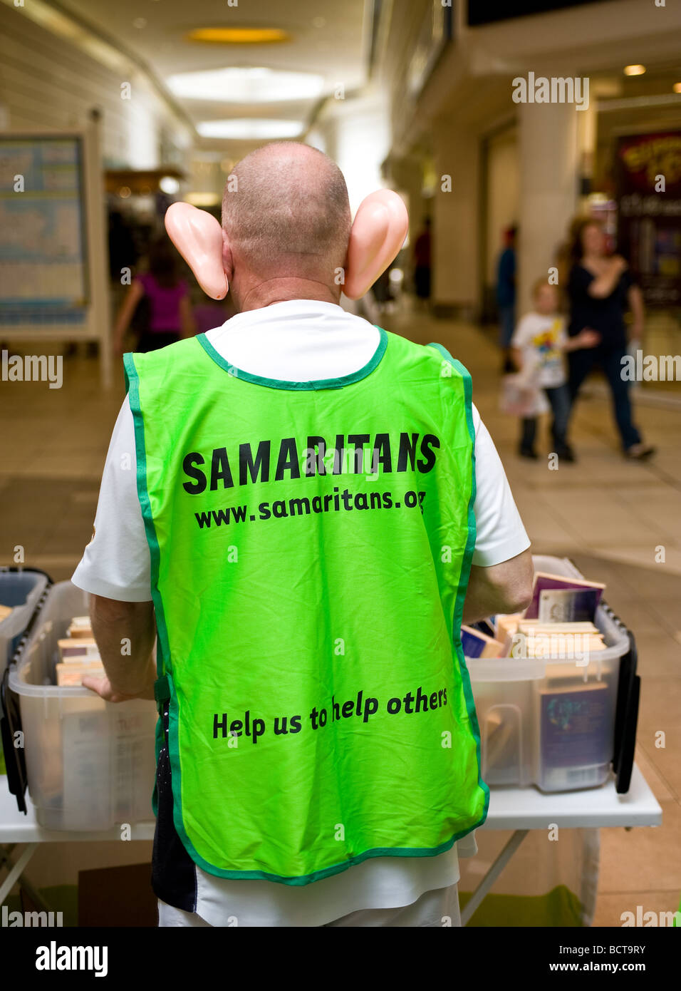 A volunteer from the charity The Samaritans fundraising whilst wearing large false plastic ears.  Photo by Gordon - Stock Image