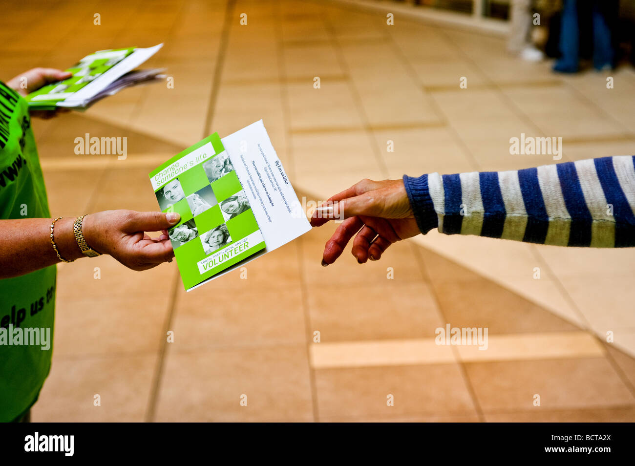 A volunteer from the Samaritans handing out leaflets. - Stock Image