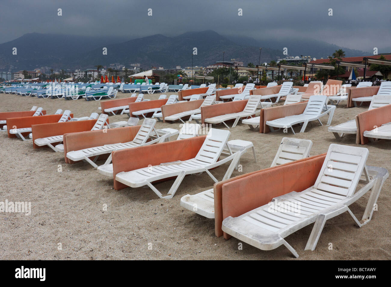 Beach chairs silhouetted against a pink sky of an evening sunset at Alanya - Stock Image