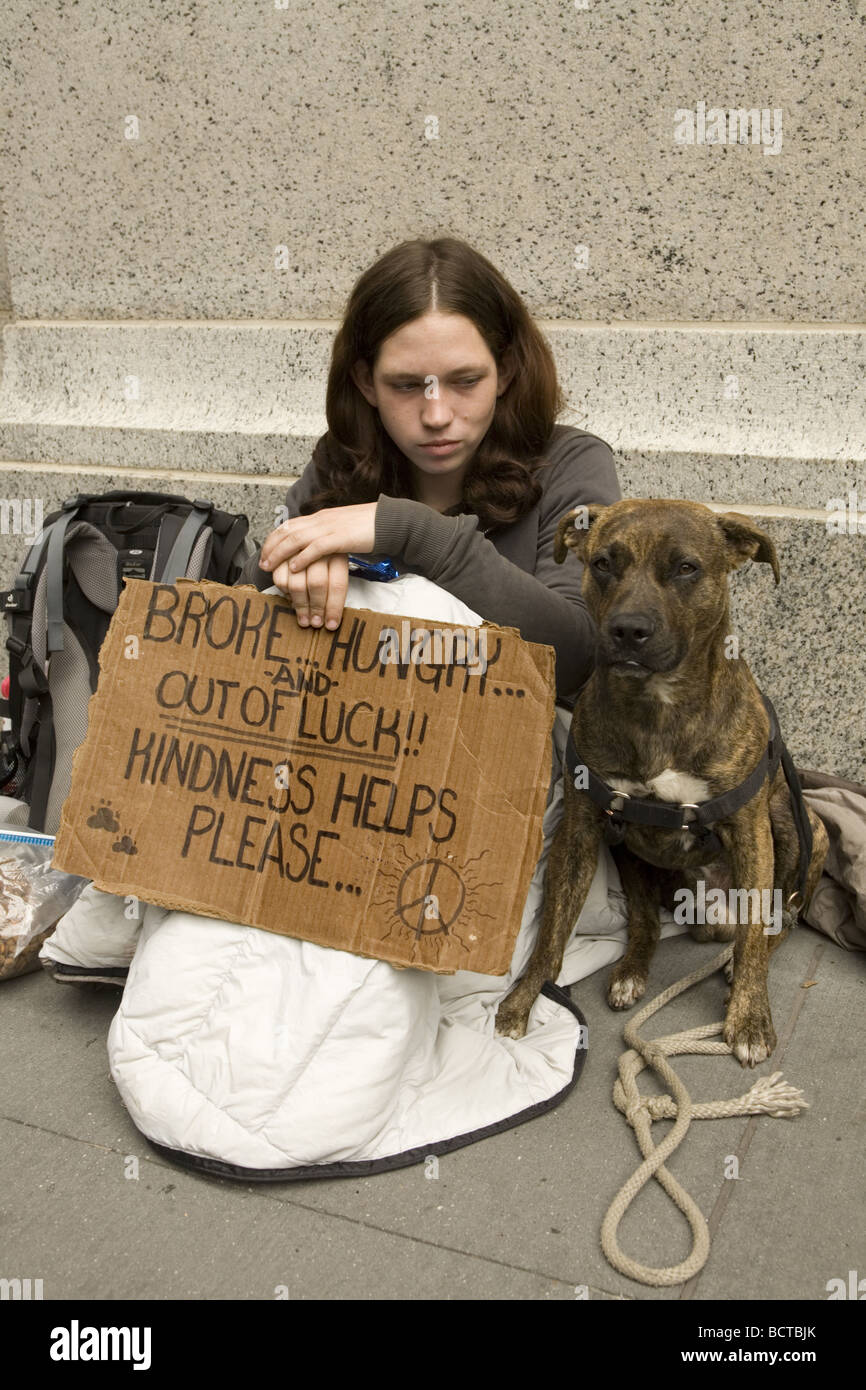 Homeless young woman panhandling on Broadway in the financial district of New York City - Stock Image