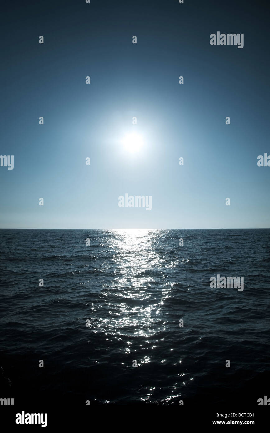 Sun over the sea horizon Soft blue tint Stock Photo