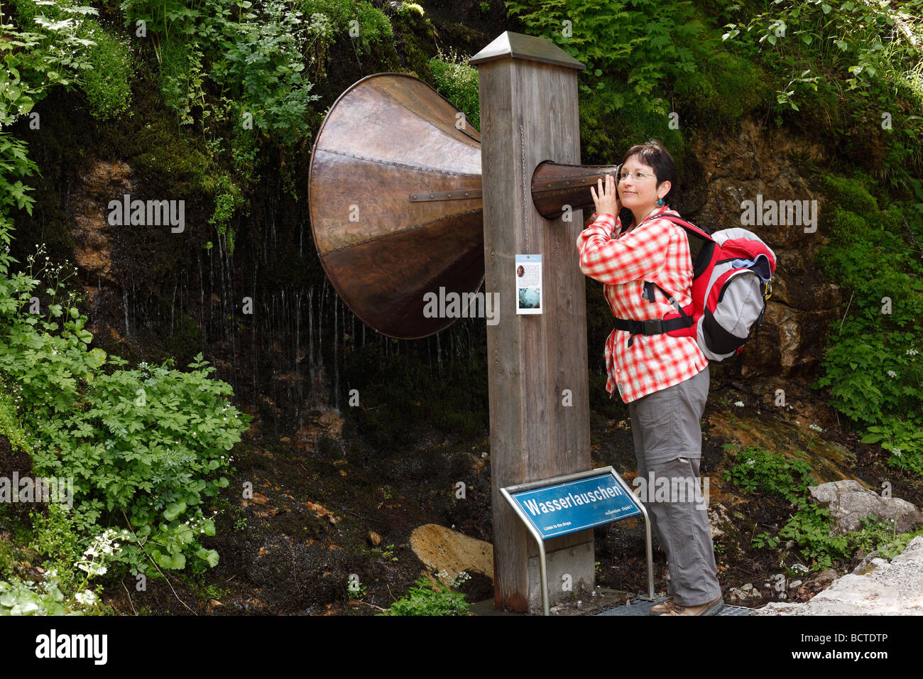 Woman with backpack listening to a copper funnel, station 'listening to water' on the water themed hiking - Stock Image