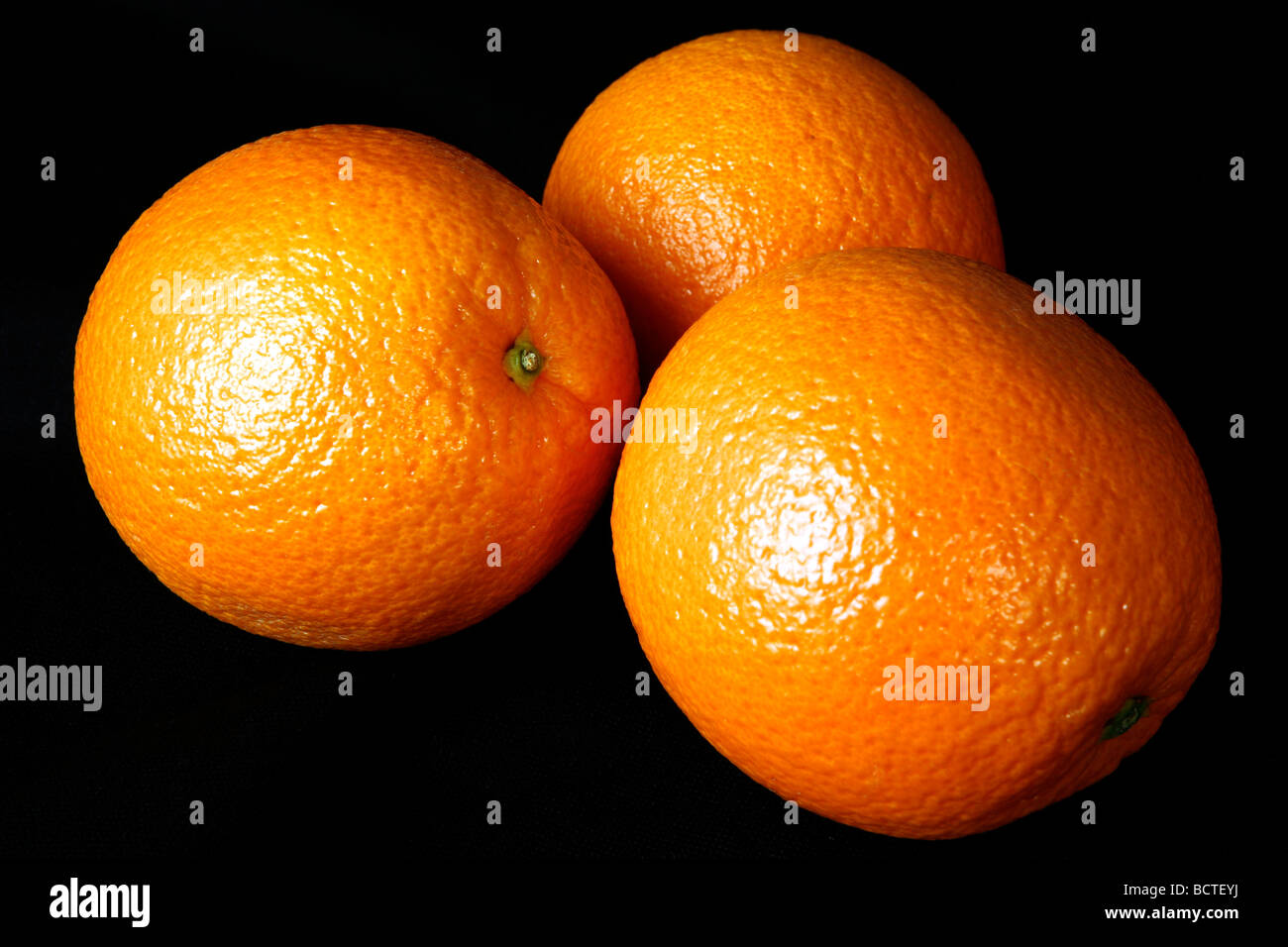 Three oranges placed against a black background - Stock Image