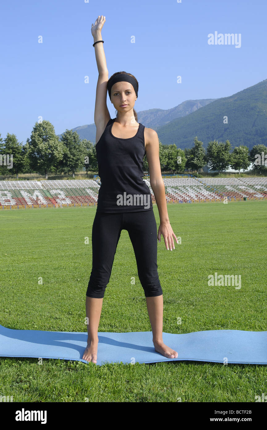 Girl doing standing stretching exercise for the upper body - sides, shoulders arms - Stock Image