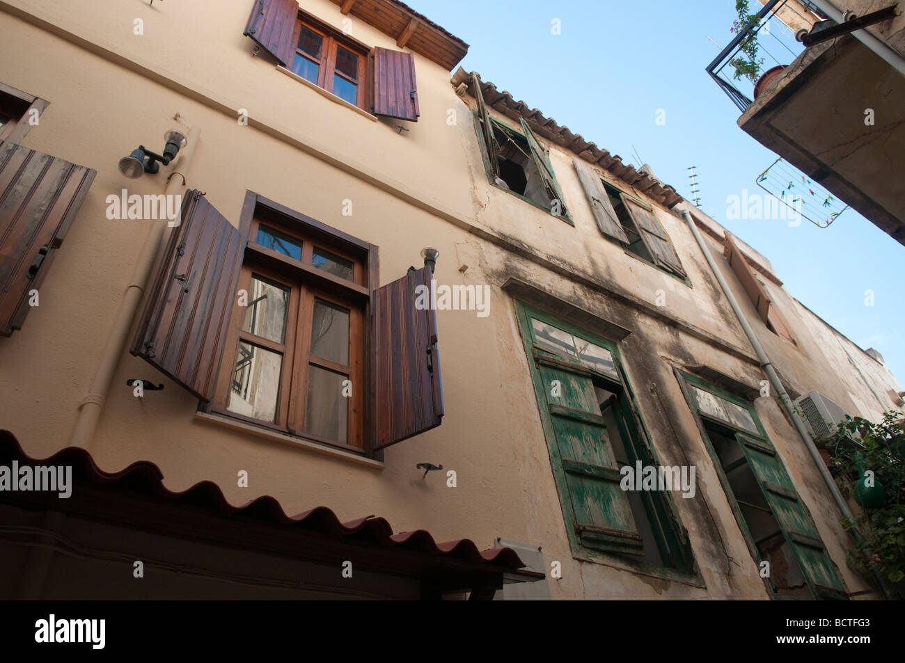 Old building with wooden window shutters. Chania, Crete, Greece. - Stock Image