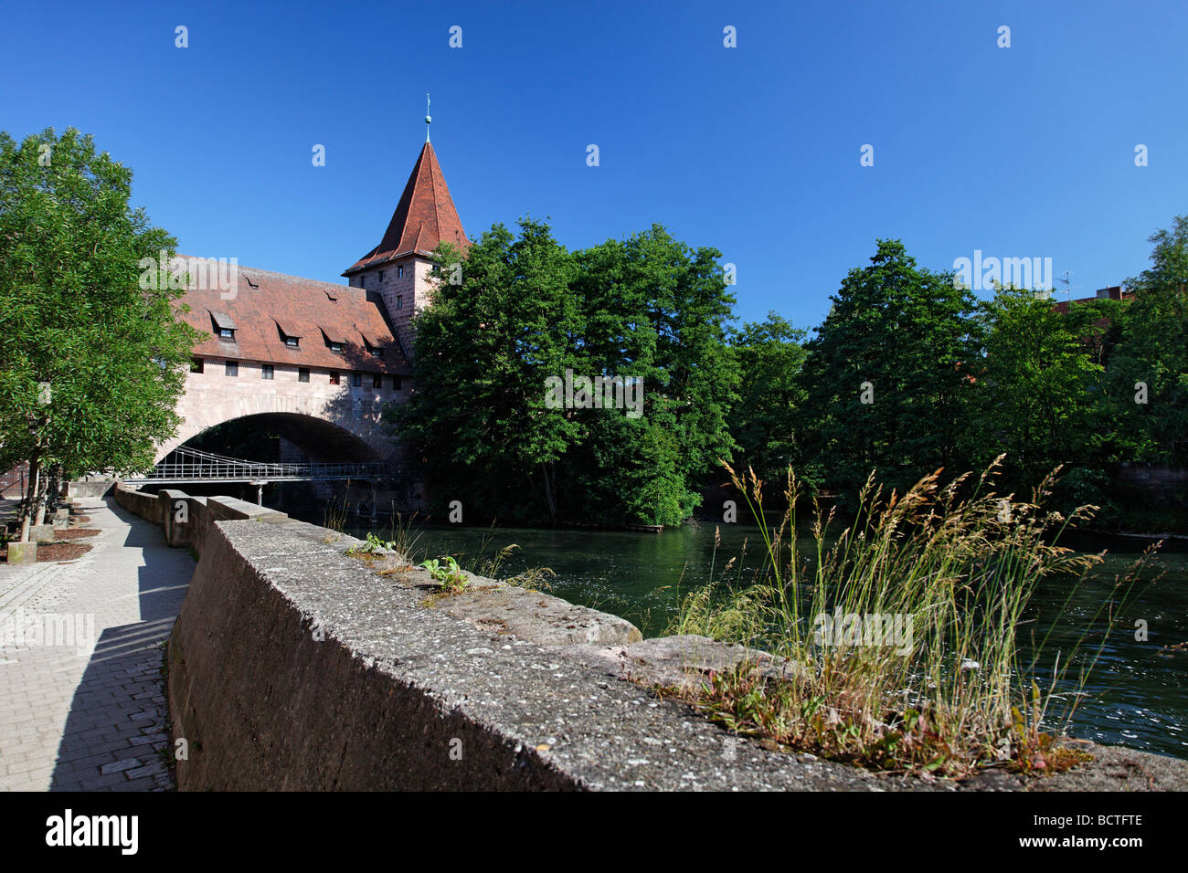 Waterside promenade with Hallertor gate, Kettensteg bridge, and Schlayerturm tower, Pegnitz river, bridge, trees, - Stock Image