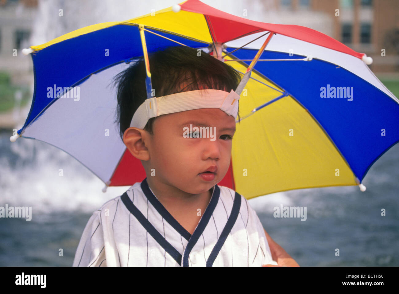 deeb55a58 A young Japanese boy wearing an umbrella hat at the Biosphere ...