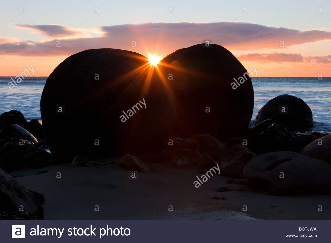 The rising sun shines between two of the Moeraki Boulders located at Koekohe Beach along Otago coast of New Zealand. - Stock Image