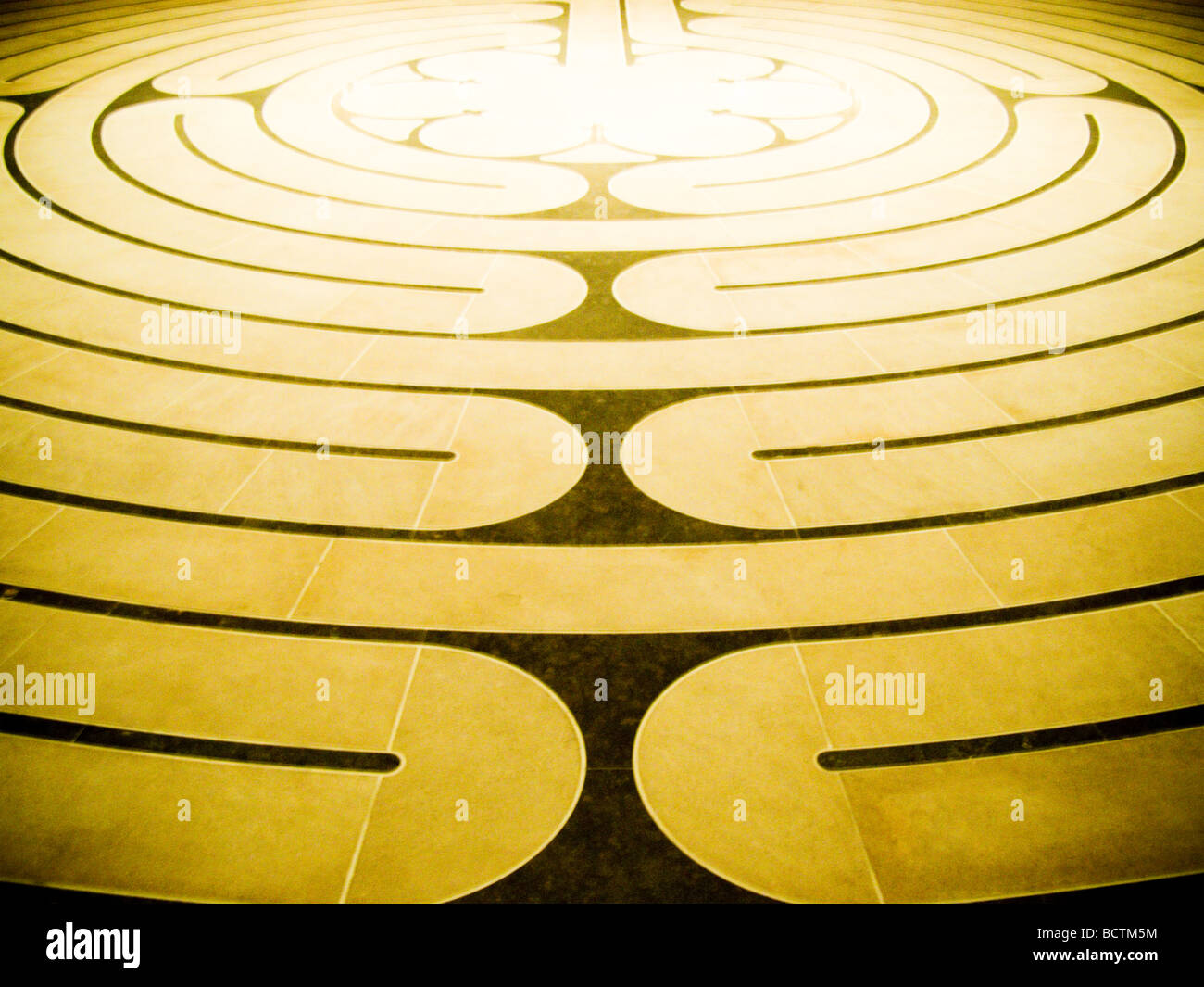 Brown and golden spiral maze floor pattern - Stock Image