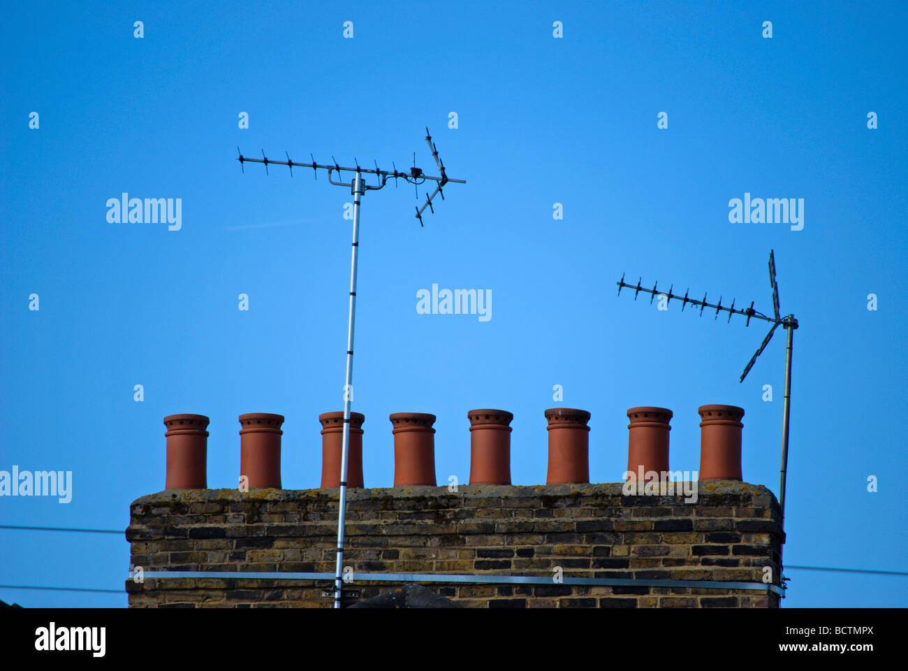row of chimey pots and two tv aerials on a rooftop of victorian homes in barnes, southwest london, england - Stock Image