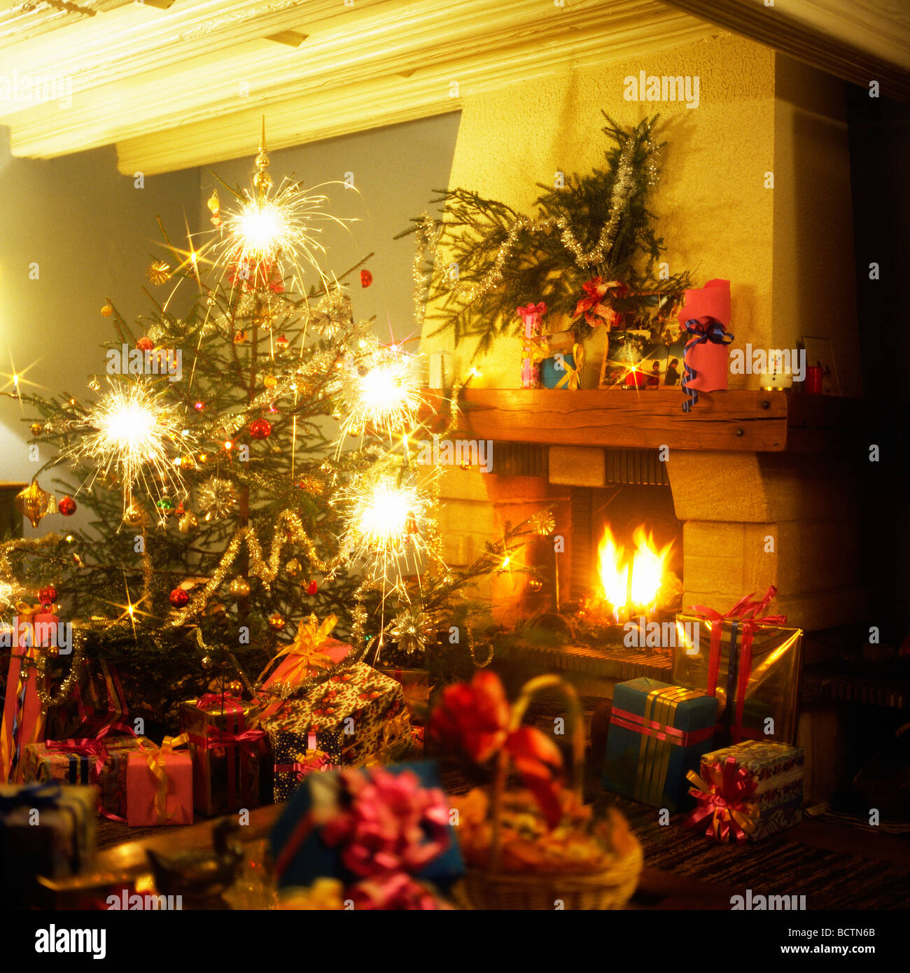 CHRISTMAS PRESENTS UNDER THE TREE WITH SPARKLERS AND FIREPLACE Stock Photo