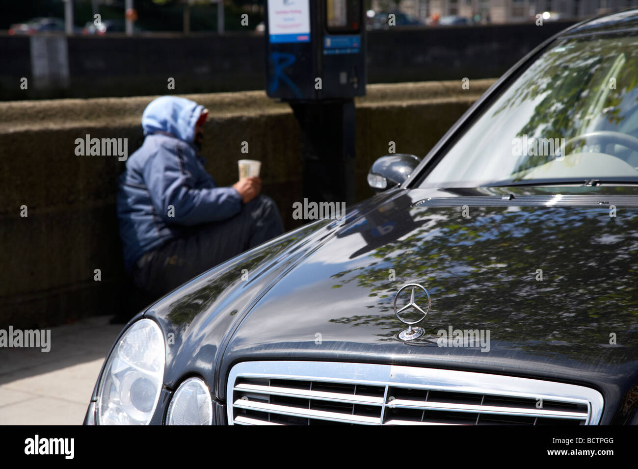 street beggar lying beside a parking ticket machine and mercedes car looking for spare change dublin city - Stock Image