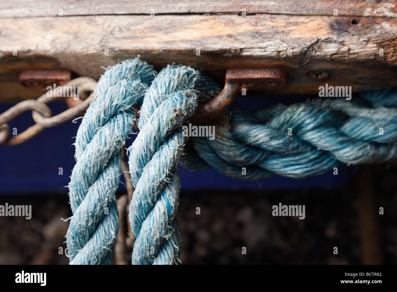 Close up of blue ropes attached to a rusty metal hook on an old boat - Stock Image