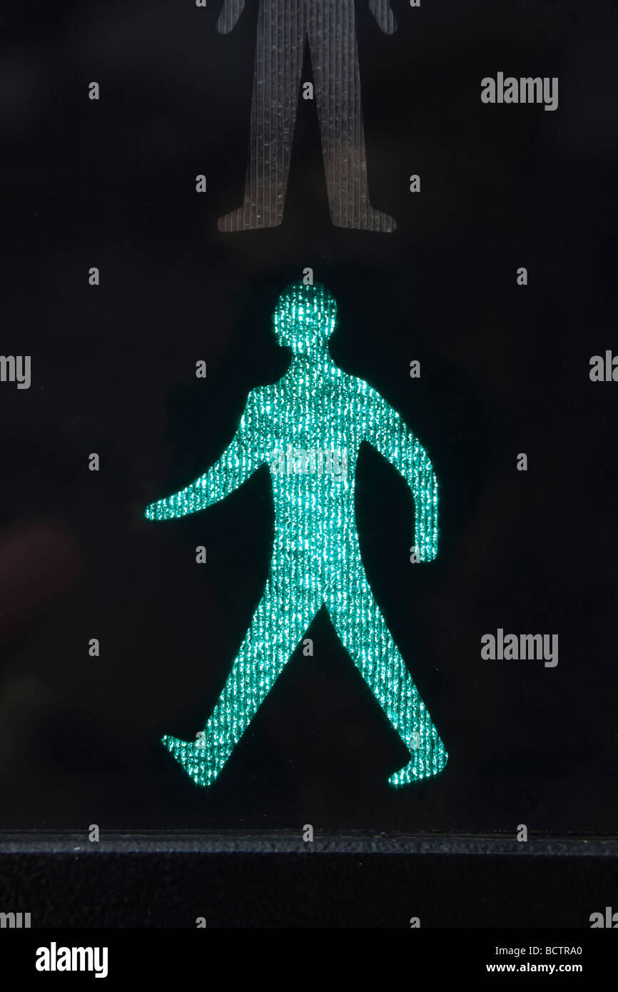 Close up of illuminated walking green man safe to cross road symbol on a pedestrian crossing traffic lights. England - Stock Image