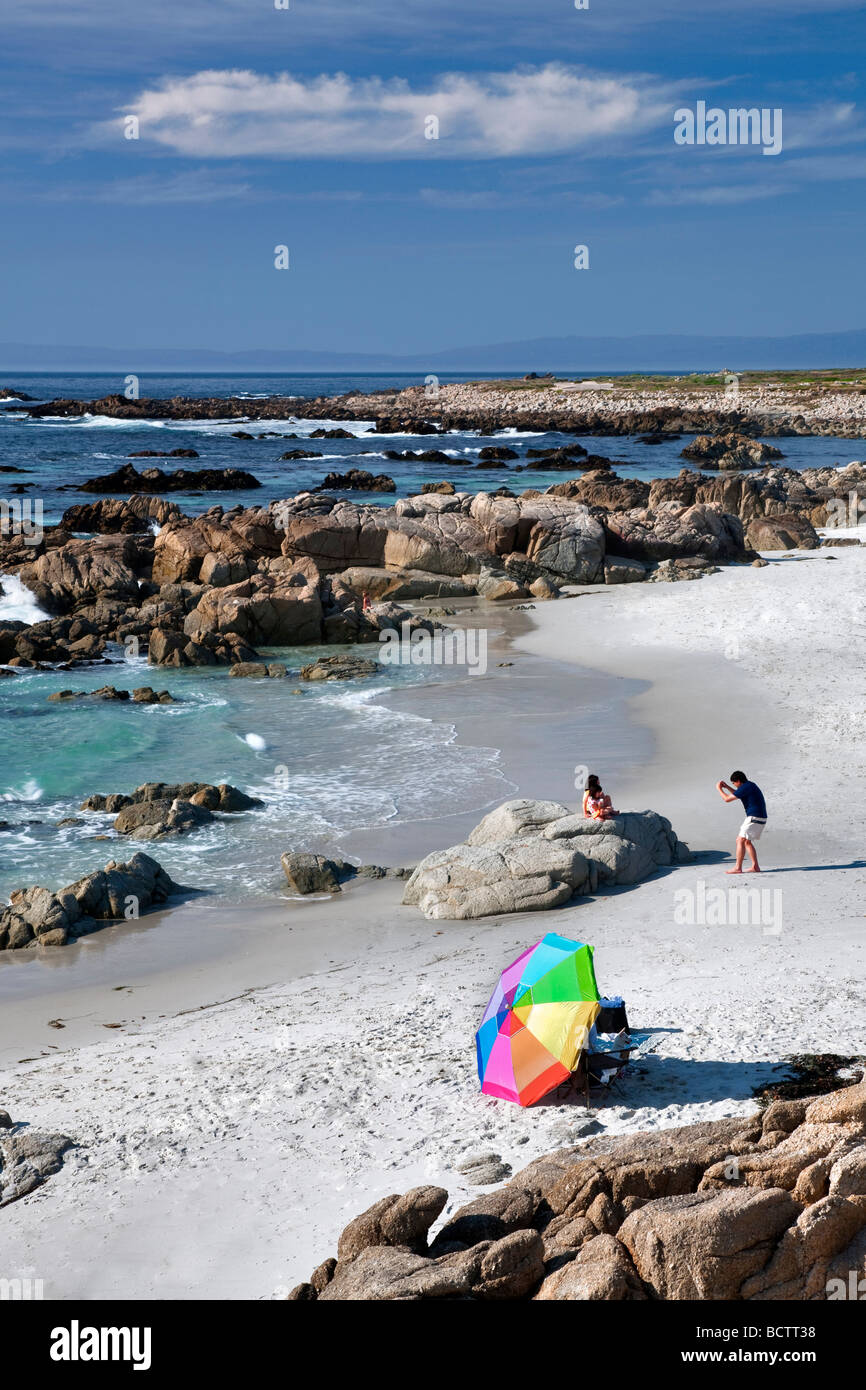 Beach umbrella and beach with man taking picture of family 17 Mile Drive Pebble Beach California - Stock Image