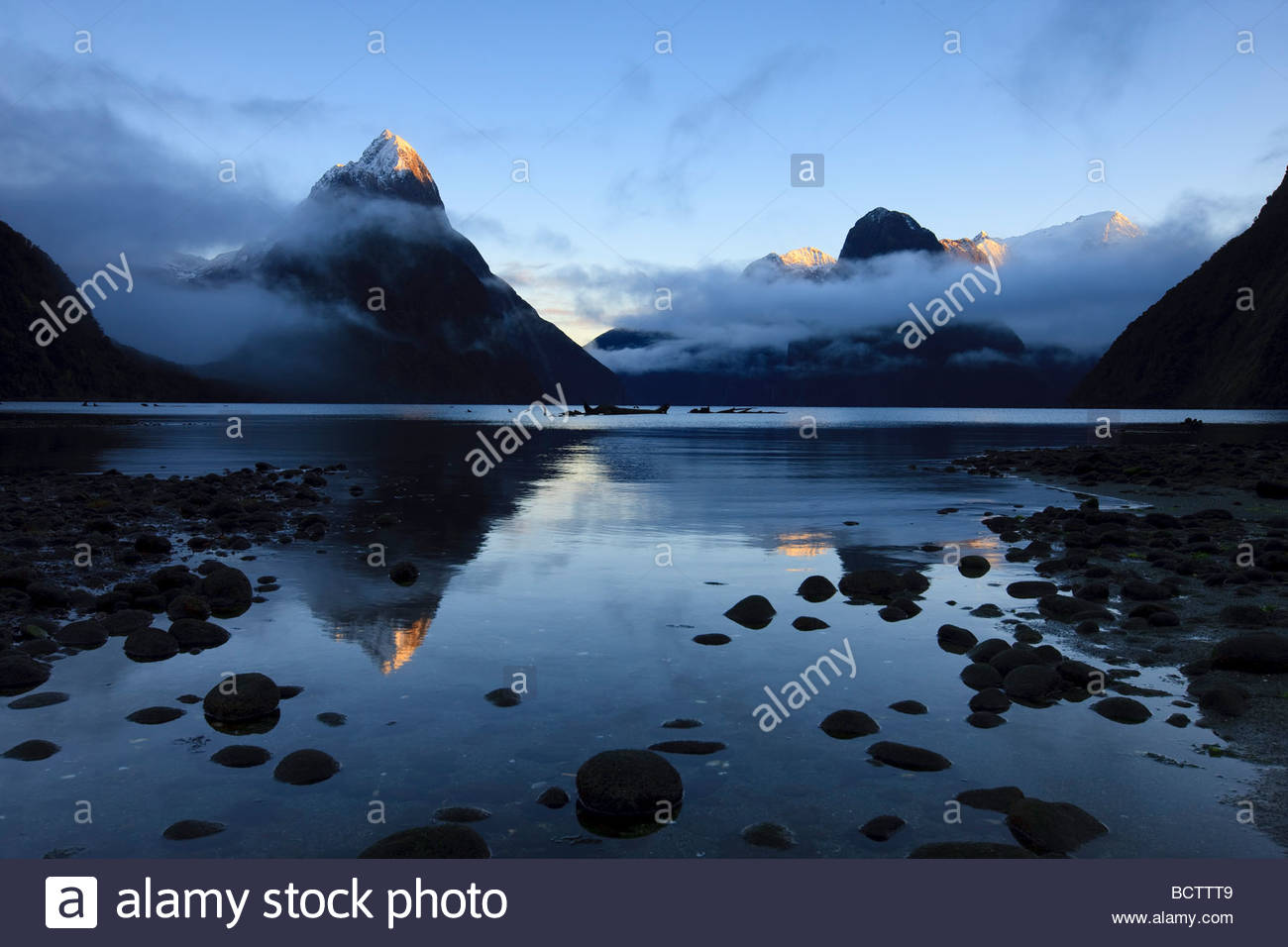 Mitre Peak, Mount Pembroke, and other mountains in Fiordland National Park, New Zealand, are reflected in Milford - Stock Image