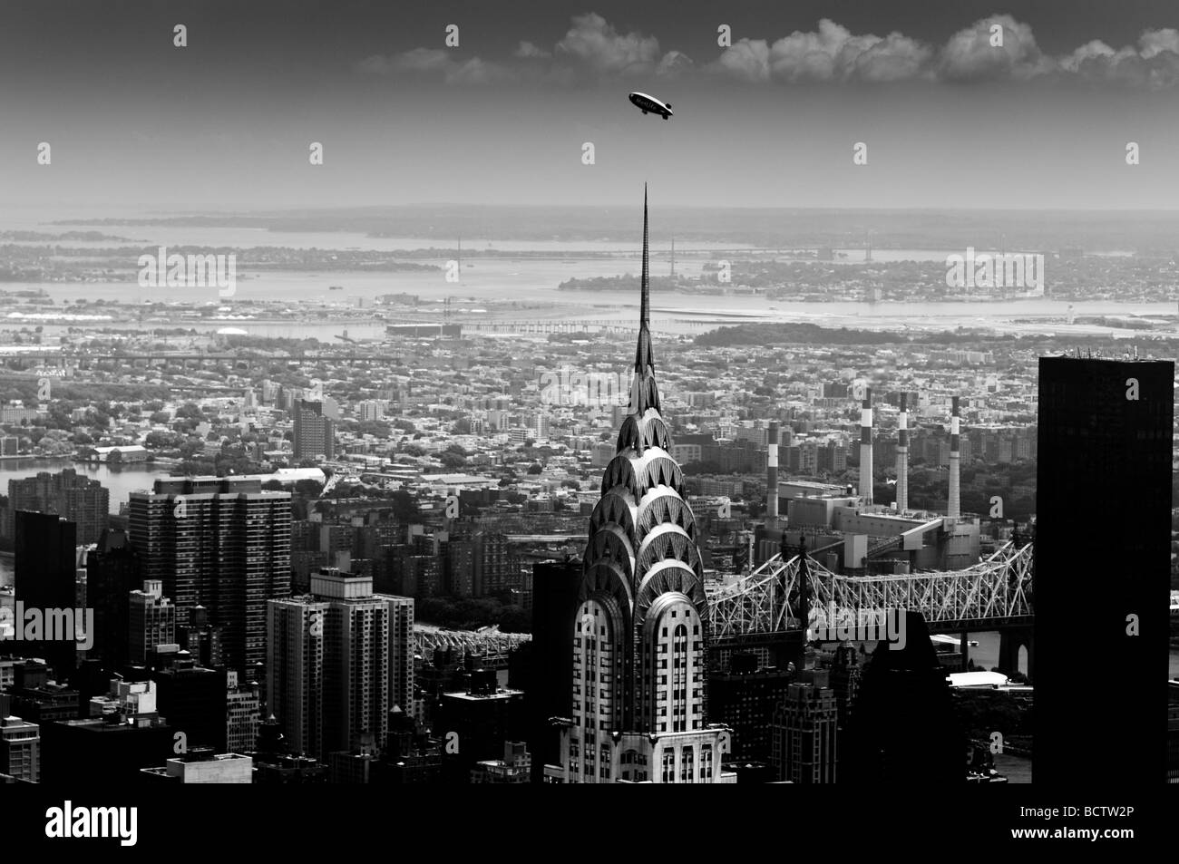 The Crystler Building with a Goodyear blimp flying overhead seen from the top of the Empire State Building - Stock Image